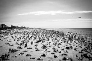 Scheveningen- waar het krioelt van de mensen.  Deze foto is genomen vanaf de linkerkant van de pier. Het zonlicht dat op het zand schijnt, springt in het oog.